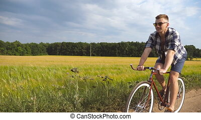 Sporty guy in sunglasses cycling along country trail...