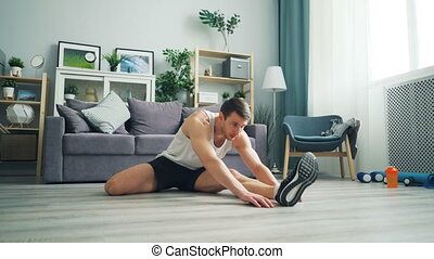 Sporty guy stretching sitting on floor bending to leg...