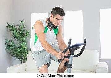 Sporty handsome man training on exercise bike using tablet