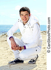 Sporty happy handsome man  on the beach, white suit, outdoors, freedom