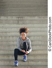 sporty, młoda kobieta, posiedzenie na kroczy, wiążąc bucik, koronka