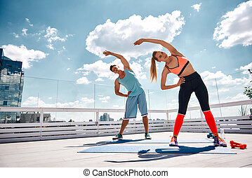 Sporty male and female are doing fitness on rooftop