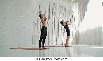Sporty man and woman doing ashtanga yoga