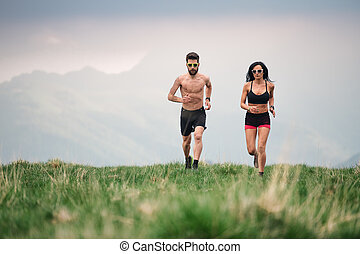 Sporty man and woman run hot in the summer on hill meadows
