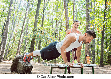 Sporty man doing push-up in an outdoor gym