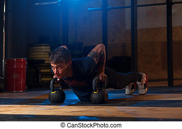 Sporty man doing push ups with kettle bells