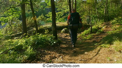Sporty man with large backpack walks down steep mountain path at sunset