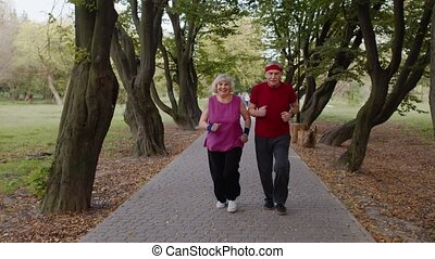 Sporty mature couple family jogging together. Senior husband and wife doing cardio workout exercises