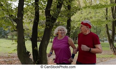 Sporty mature family couple jogging together. Senior husband and wife doing cardio workout exercises