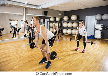 Sporty Men And Women Lifting Barbells In Gym