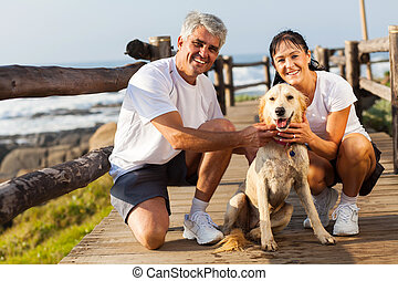 sporty middle aged couple and pet dog at the beach in the ...