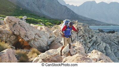 Sporty mixed race man with prosthetic leg hiking - Fit, ...