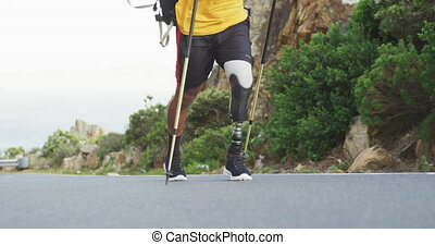 Sporty mixed race man with prosthetic leg hiking - Low angle...