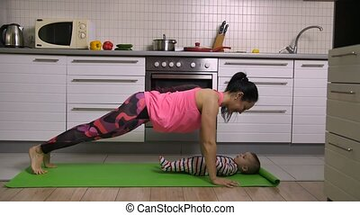 Sporty mother kissing baby doing plank excercise