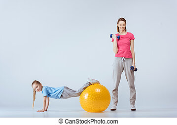 sporty mother with dumbbells and daughter with fitness ball excising together