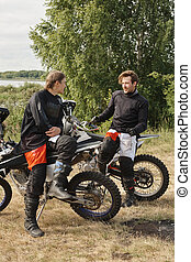 Sporty motorcyclists resting after race