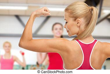 sporty, mulher, mostrando, dela, bíceps