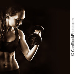 sporty muscular woman training with dumbbells on black