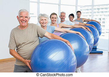 Sporty people carrying exercise balls in bright gym -...