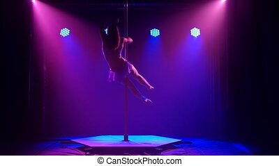 Sporty pole dance performed by a slender young woman. Beautiful gymnastic movements in slow motion. Demonstration of a flexible body. Silhouettes in a beautiful studio light