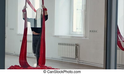 Sporty pole dancer on aerial silk in studio