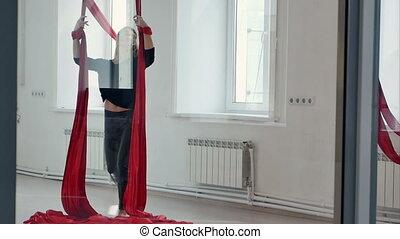Sporty pole dancer on aerial silk in studio. Slow motion. ...