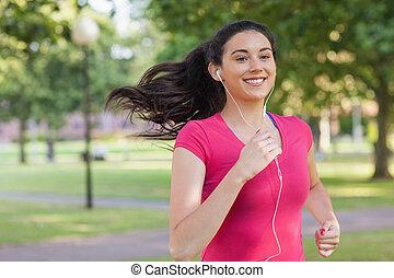 Sporty pretty woman jogging in a park