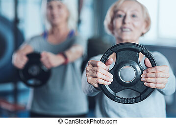 Sporty retired lady holding weight disk at fitness club