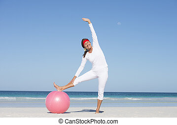 Sporty senior woman active at beach