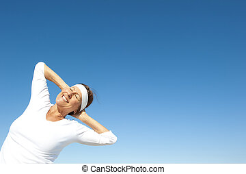 Sporty senior woman sky background