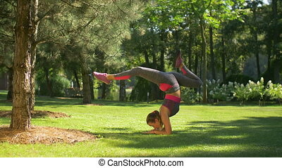 Sporty slim woman doing handstand exercise on grass - Active...