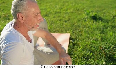 Sporty smiling aged man resting after sport exercises in the park