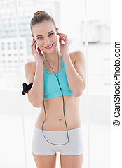 Sporty smiling woman listening to