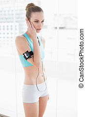 Sporty stern woman listening to music in bright room
