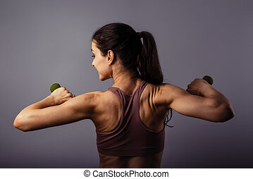 Sporty strong healthy happy woman training with dumbbells in hands in sport top on violet background. Closeup portrait. Back view. The concept