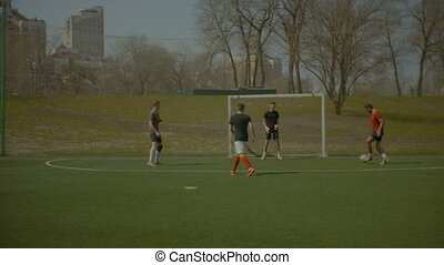 Sporty teenagers playing soccer on the sports field