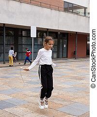 Sporty tween girl jumping rope in school yard during recess
