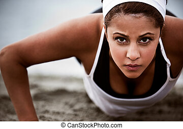 Sporty woman - A beautiful asian woman doing push up at a...