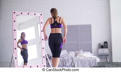 Sporty woman admiring her body shape in mirror