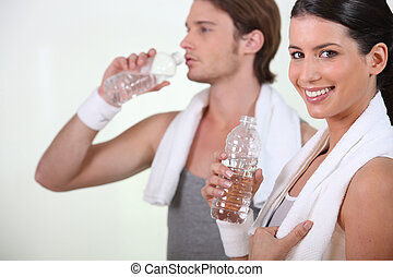Sporty woman and man drinking water on white background