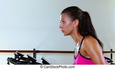Sporty woman at the gym on bike. Sunny gym