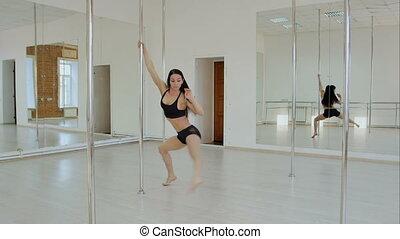 Sporty woman balancing on pylon at dance studio....