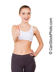 Sporty woman. Beautiful young woman in sports clothing showing her thumb up and smiling while standing isolated on white
