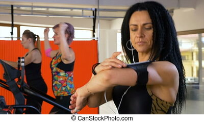 Sporty woman checking fitness tracker app on smartphone...