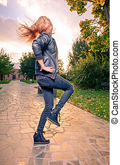 Sporty woman dancing in urban park on paved lane with her leg raised in air and head shaking