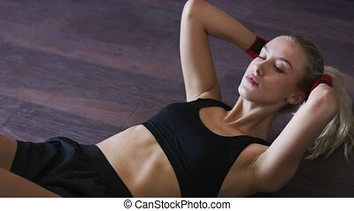 Sporty woman doing abdominal crunches on floor