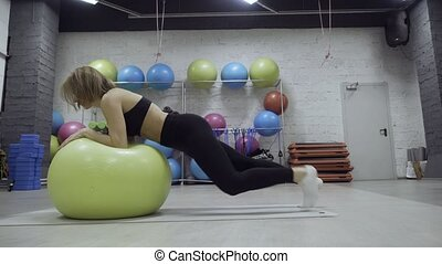 Sporty woman doing exercise with green fitball in the gym.
