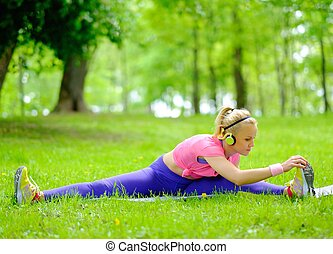 Sporty woman doing fitness exercises outdoors