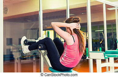 Sporty woman doing sit-up using training apparatus in a gym