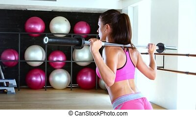 Sporty woman doing squat workout in gym